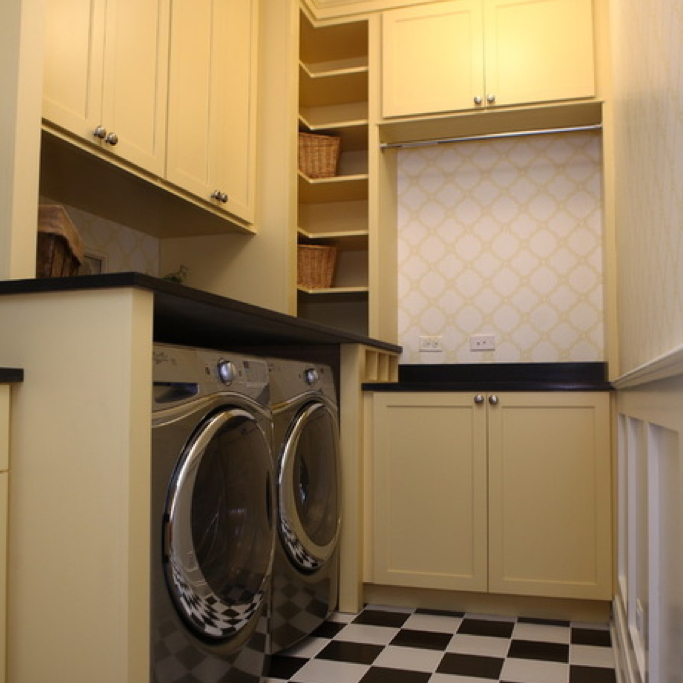 Laundry room with yellow storage cabinets